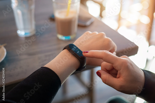 Fotografía Girl uses apss on her smart band to view health parameters
