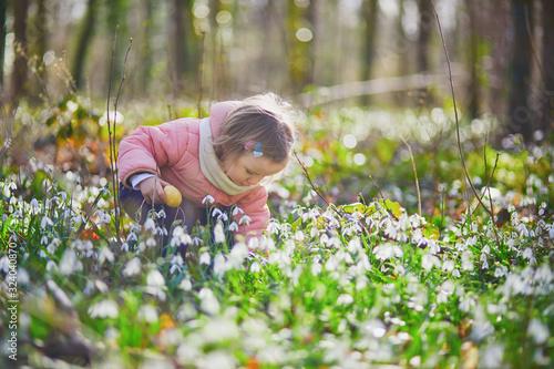 Valokuva Cute little girl playing egg hunt on Easter