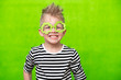 Leinwanddruck Bild - portrait little smiling caucasian boy in mask of leprechaun shamrock clover glasses for irish St. Patrick's Day on green studio background. Copyspace.