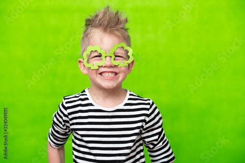 Valokuvatapetti portrait little smiling caucasian boy in mask of leprechaun shamrock clover glasses for irish St