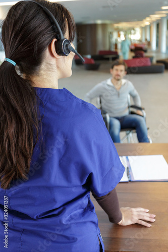 Fototapeta hospital receptionist and approaching patient in wheelchair obraz