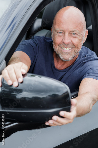 Fototapeta close-up of a mature man fixing the side mirror obraz
