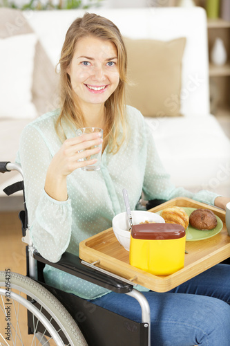 Fototapeta thoughtful woman in a wheelchair drinking coffee in the morning obraz