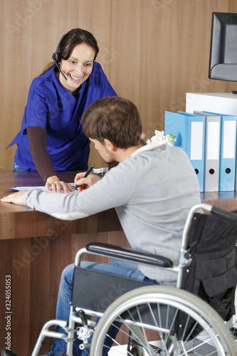 Fototapeta disabled man sitting on wheelchair talking to female receptionist obraz