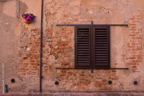 Vintage classic window on old brick wall with closed wooden shutters