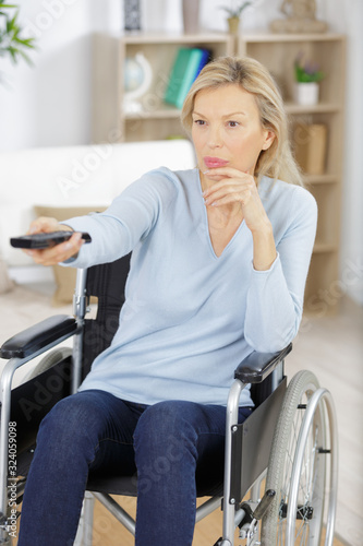 Fototapeta disabled woman in wheelchair watching movies at home obraz