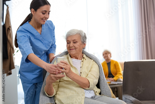 Fotomural Care worker giving water to elderly woman in geriatric hospice