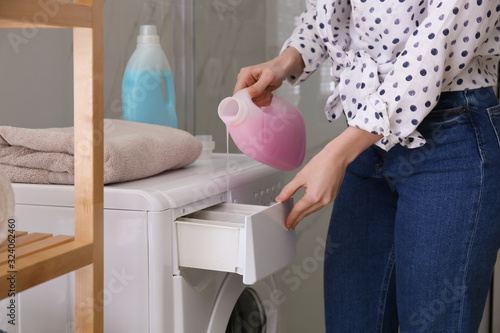 Fotografia Woman pouring detergent into washing machine drawer in bathroom, closeup
