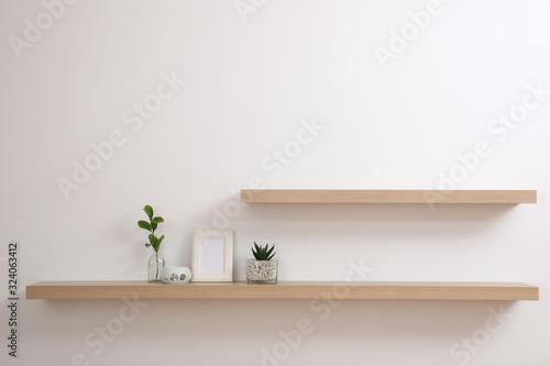 Fényképezés Wooden shelves with plants and photo frame on light wall