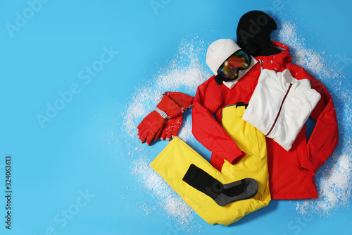 Stylish winter sport clothes on light blue background, flat lay. Space for text