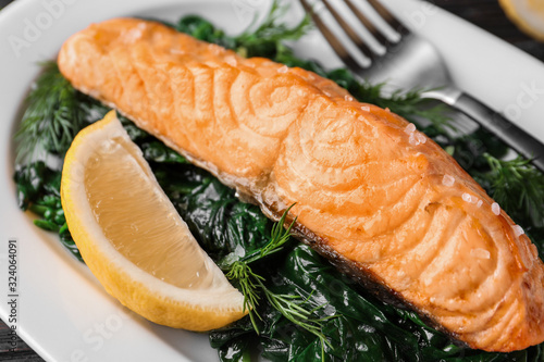 Tasty salmon with spinach and lemon on plate, closeup