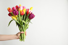 Woman Holding Beautiful Spring Tulips On White Background, Closeup. Space For Text