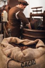 Jute Bag Full Of Cocoa Beans In A Chocolate Maker Workshop, With A Male Chocolatier Working On Conching And Melanger Equipment On The Background