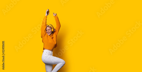 Obraz na plátně Stunning blonde caucasian girl dressed in an orange sweater and white jeans is d