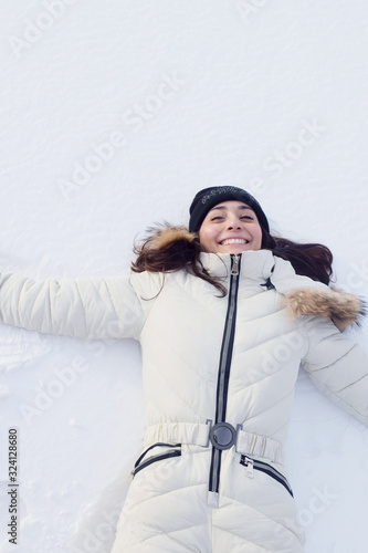 blissful young woman laying in the snow Canvas Print
