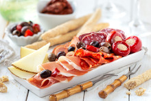 Delicious Meat Platter With Cheese, Spicy Olives And Stuffed Cherry Pepper Served As An Appetizer With Bread Sticks. Traditional Spanish Tapas With Ham, Choriso, Lomo Iberico, Fuet And Goat Cheese