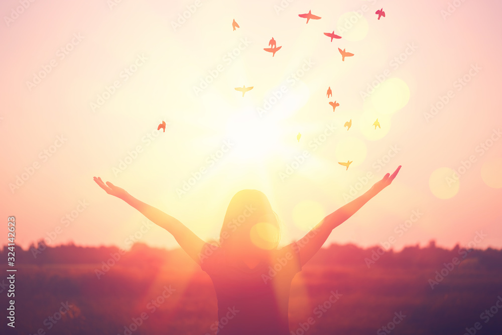 Fototapeta Freedom and feel good concept. Copy space of silhouette woman rising hands on sunset sky background.