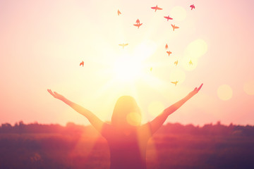 Freedom and feel good concept. Copy space of silhouette woman rising hands on sunset sky background.