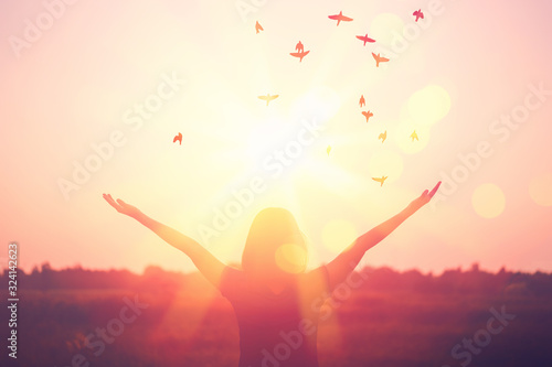 Fototapeta Freedom and feel good concept. Copy space of silhouette woman rising hands on sunset sky background. obraz