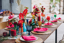 Banquet Tables Decorated In Tropical Style Decor, Dishes On The Tables With Pink Napkins, Glasses, Candles, Colorful Flowers
