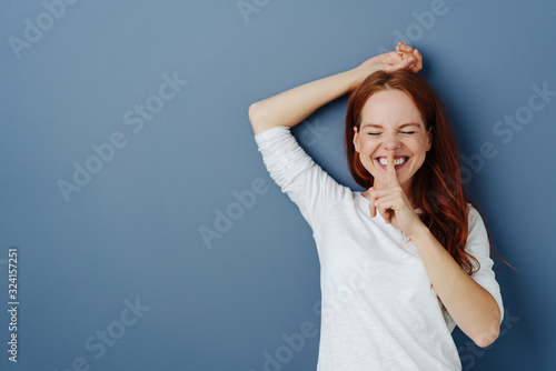 Obraz Cute charismatic young woman with finger to lips - fototapety do salonu