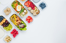 Lunch Boxes With Healthy Food And Ingredients On White Background