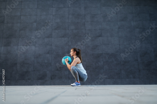 Obraz na plátně Side view of caucasian sportswoman in shape holding weight ball while crouching and doing endurance