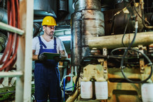 Attractive Caucasian Mechanic In Overalls And With Helmet On Head Standing Inside Of Ship, Holding Tablet And Checking On Engine.