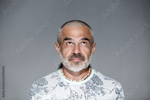 Tablou Canvas Friendly mature man with short hair and white grey beard  looking upwards over g