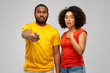Leinwanddruck Bild - entertainment and people concept - african american couple with tv remote control over grey background