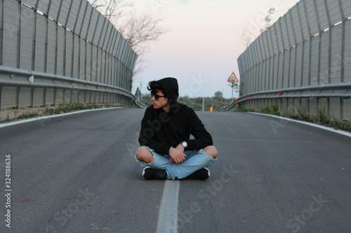 Fototapeta Uomo seduto per strada