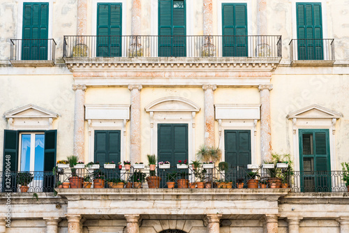 Photo historical building with shutters, balcony and flower pots