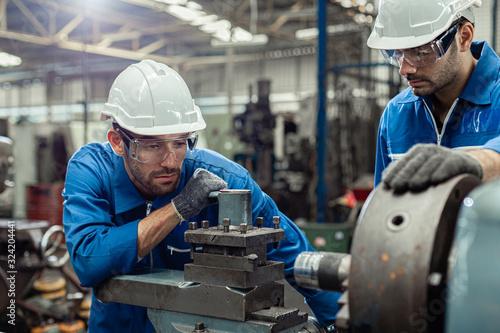 Obraz Engineer men wearing uniform safety in factory working machine lathe metal. - fototapety do salonu