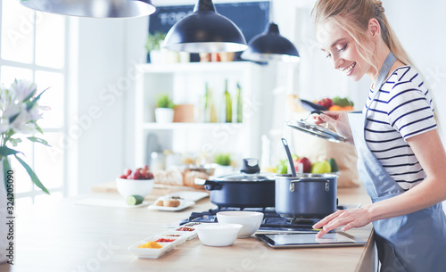 Fototapeta Young woman using a tablet computer to cook in her kitchen obraz