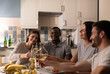 Diverse couples proposing toast during party