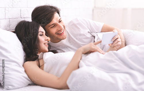 Young married couple watching photos on cellphone