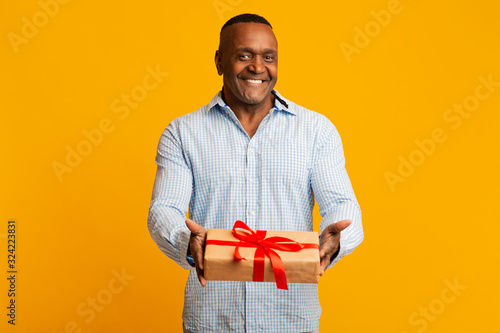 Happy mature african american man giving gift box on camera