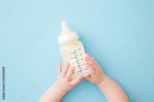 Fotografia Infant hands holding  bottle of milk on light blue floor background