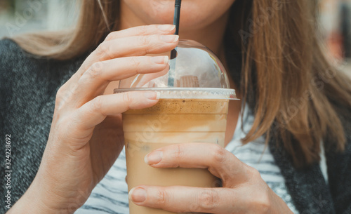 Fototapeta Woman's hand holding cold Frappe Coffee. obraz
