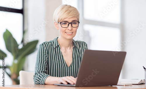 Vászonkép Lady Working On Laptop Typing Business Report Sitting In Office