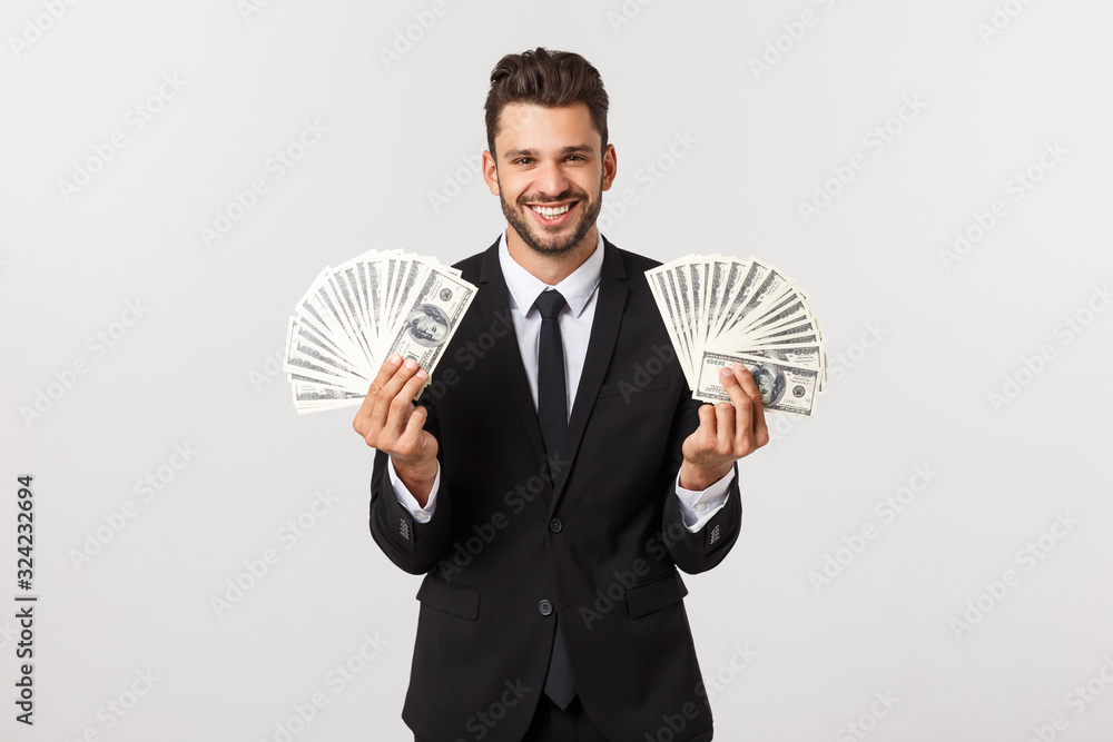 Fototapeta Portrait of a satisfied young businessman holding bunch of money banknotes isolated over white background.