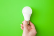 canvas print picture - Young man hand holding led light bulb on bright green table background. Closeup. Energy saving. Point of view shoot. Top down view.