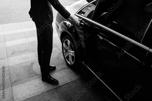 Fototapeta Valet's Hand Opening Grey Car Door On Street