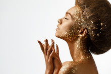 Fashion Art Portrait Of Model Girl With Holiday Golden Shiny Professional Makeup. Woman With Gold Metallic Body And Hair On White Background. Gold Glowing Skin. Copy Space
