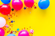 Decorative frame with colorful balloons on yellow background top-down frame copy space