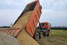 A Dump Truck Unloads Sand At A Construction Site.
