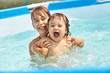 children playing in swimming pool. relaxing two sisters.