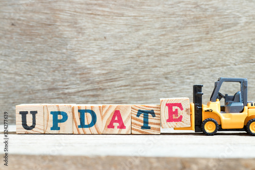 Photo Toy forklift hold letter block e to complete word update on wood background
