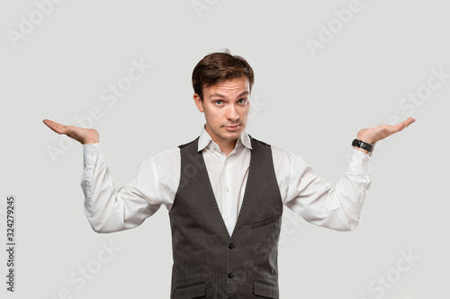 Fotografering Young man in a white shirt and grey vest shrugging his shoulders expressing emotion of confusion