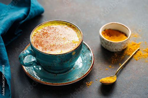 Closeup view of turmeric latte cup on a textured dark background. Tableau sur Toile